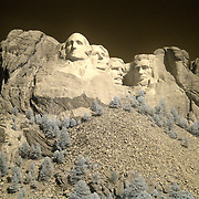 The Mount Rushmore National Memorial, near Keystone, South Dakota, is a monumental granite sculpture by Gutzon Borglum. The monument represents the first 150 years of the history of the United States of America with 60-foot (18m) sculptures of the heads of former United States presidents (left to right): George Washington, Thomas Jefferson , Theodore Roosevelt, and Abraham Lincoln. The entire memorial covers 1,278.45acres (5.17km2) and is 5,725feet (1,745m) above sea level...This is an infrared image which captures light that we cannot see and turns it into a visible image. Plants like flowers and grass reflect more infrared light and appear brighter in infrared images while the sky reflects less making it darker.