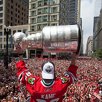 Chicago Blackhawks player, Patrick Kane holds the Stanley Cup high as thousands of fans look on during the Hawks Championship parade.