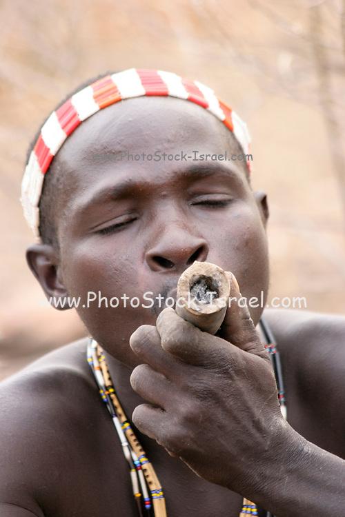 Africa, Tanzania, Lake Eyasi, Hadza man smoking from a traditional clay pipe Small tribe of hunter gatherers AKA Hadzabe Tribe October 2008