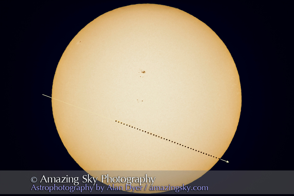 A composite image of the May 9, 2016 transit of Mercury across the Sun, with Mercury at a perfect &ldquo;inferior conjunction&rdquo; between the Sun and Earth. Transits happen only rarely, about 13 per century. The next is November 11, 2019. Then in 2032.<br /> <br /> From my location in Kamloops, British Columbia the early stages of the transit were not visible (the transit was in progress at sunrise) and for the first hour or so after sunrise clouds close to the horizon prevented me from starting a consistent sequence of images until about 7:00 a.m. PDT, some 3 hours into the 7-hour-long transit. <br /> <br /> From then on I took images every 30 seconds. For this composite I used every 14th image to create a sequence showing Mercury moving across the Sun at 7 minute intervals, until it egressed at lower right at about 11:38 a.m. PDT. I stacked a total of 40 images.<br /> <br /> For all images I used the 130mm f/6 Astro-Physics refractor with a 2X Barlow for an effective focal length of 1560mm and the Canon 60Da camera (at ISO 100) to yield an image size with the Sun just filling the frame. Exposures were 1/250th second through a Kendrick white light Mylar filter. Yellow colouration of the solar disk added in processing. The telescope was on the Mach 1 equatorial mlount tracking the Sun though imperfectly polar aligned, requiring manual alignment of the disk images in Photoshop to compensate for the image drift.<br /> <br /> The 40 images of Mercury are not all perfect dots nor equal in size due to the variations in seeing conditions from frame to frame. Some frames were sharper than others. I&rsquo;ve not &ldquo;cheated&rdquo; and placed a perfectly sharp disk image cloned and positioned across the Sun to create a more perfect simulation. <br /> <br /> The solar disk however, comes from just one of the frames toward the middle of the sequence in mid-morning, when seeing conditions were best. Stacking all the disk images would produce smeared sunpsots and disk detail due to the rotation of the Sun over the 4.5 hours of this sequence. The other