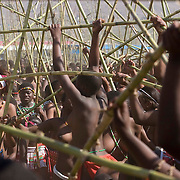 Young girls and women scramble to get reeds at the Zulu royal palace in Nongoma at the Zulu royal palace in Nongoma, KwaZulu Natal, South Africa Sept 8, 2007. Thousands of virgin girls attend the annual Reed Dance at the Enyokeni palace from which the Zulu King Zwelethini may choose a bride. Photo Greg Marinovich / Bloomberg News