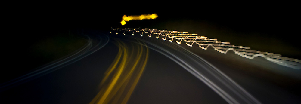 an abstract image of a curve in the road in the forest at night panorama