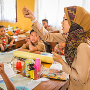 CAPTION: Grade 5 students learn about climate change and alternative forms of energy. In conjunction with various other stakeholders, the University of Lampung has prepared hands-on educational materials on climate change adaptation for teachers to use in the classroom. In SDN 1 and other pilot schools, climate change has now been integrated into the school's curriculum. LOCATION: SDN 1 School, Langkapura, Bandar Lampung, Indonesia. INDIVIDUAL(S) PHOTOGRAPHED: Yuni Purbaningsih (teacher).
