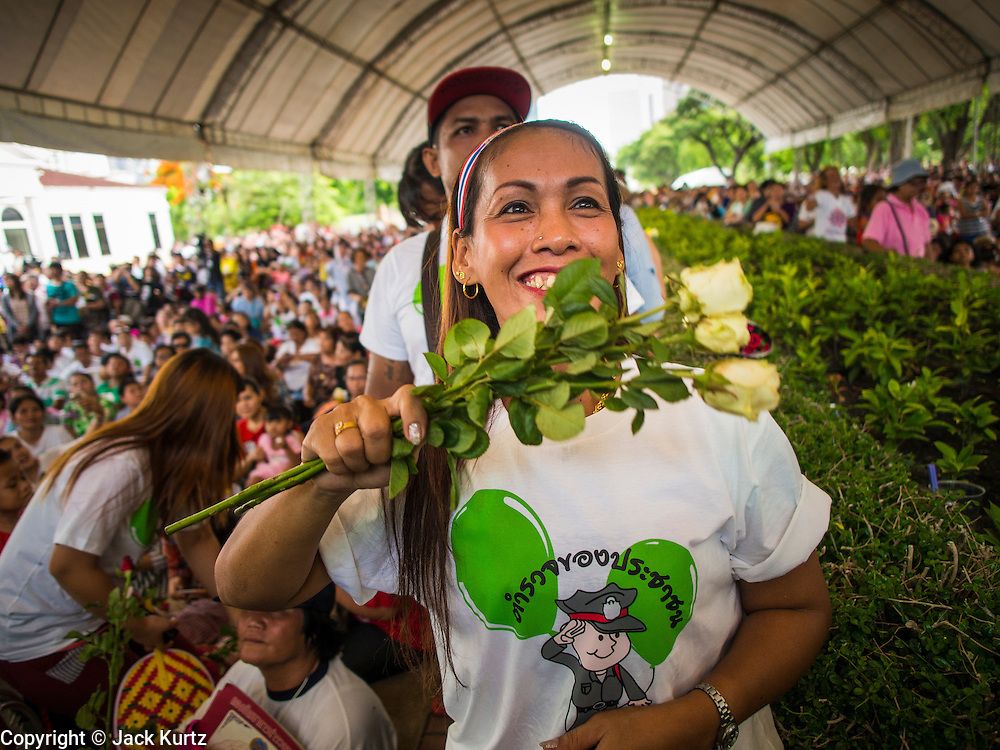 """15 JUNE 2014 - BANGKOK, THAILAND: A Thai woman waves white roses towards members of a police band during a """"Restore Happiness to Thais"""" party in Lumpini Park in Bangkok. The Thai military junta, formally called the National Council for Peace and Order (NCPO), is sponsoring a series of events throughout Thailand to restore """"Happiness to Thais."""" The events feature live music, dancing girls, military and police choirs, health screenings and free food.   PHOTO BY JACK KURTZ"""