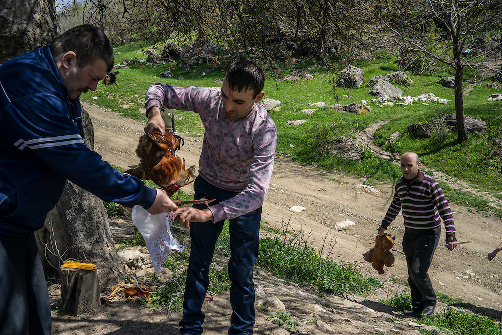 KARASHEN, NAGORNO-KARABAKH - APRIL 19: Nver Hayrapetyan, 27 (C), sacrifices a chicken in thanks after surviving a car crash on April 19, 2015 in Karashen, Nagorno-Karabakh. Since signing a ceasefire in a war with Azerbaijan in 1994, Nagorno-Karabakh, officially part of Azerbaijan, has functioned as a self-declared independent republic and de facto part of Armenia, with hostilities along the line of contact between Nagorno-Karabakh and Azerbaijan occasionally flaring up and causing casualties. (Photo by Brendan Hoffman/Getty Images) *** Local Caption *** Nver Hayrapetyan