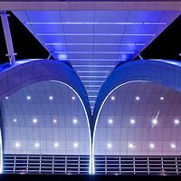 United Arab Emirates, Dubai, Colored lights adorn arched steel exterior of Dubai International Airport Terminal 3 at night