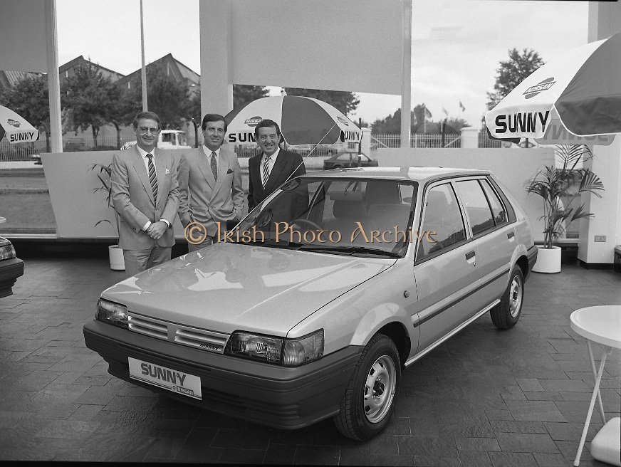 """Nissan Launches New """"Sunny""""..1986..21.08.1986..08.21.1986..21st August 1986..Nissan Ireland launched the all new integrated Sunny range on to the Irish market.The launch was the European premiere of this model and marked a significant second phase in the rationalisation of the Nissan Product range. The first Phase was the launch of the Bluebird range in February of this year. The Launch took place at Nissan House, Naas Road Dublin...Posing with the new Nissan """"Sunny"""" which was launched today were :(L - R) Mr Tony Kelly,Deputy Managing Director,Mr Gerard O'Toole,Managing Director and Mr Michael Murphy,Sales Director of Nissan Ireland."""