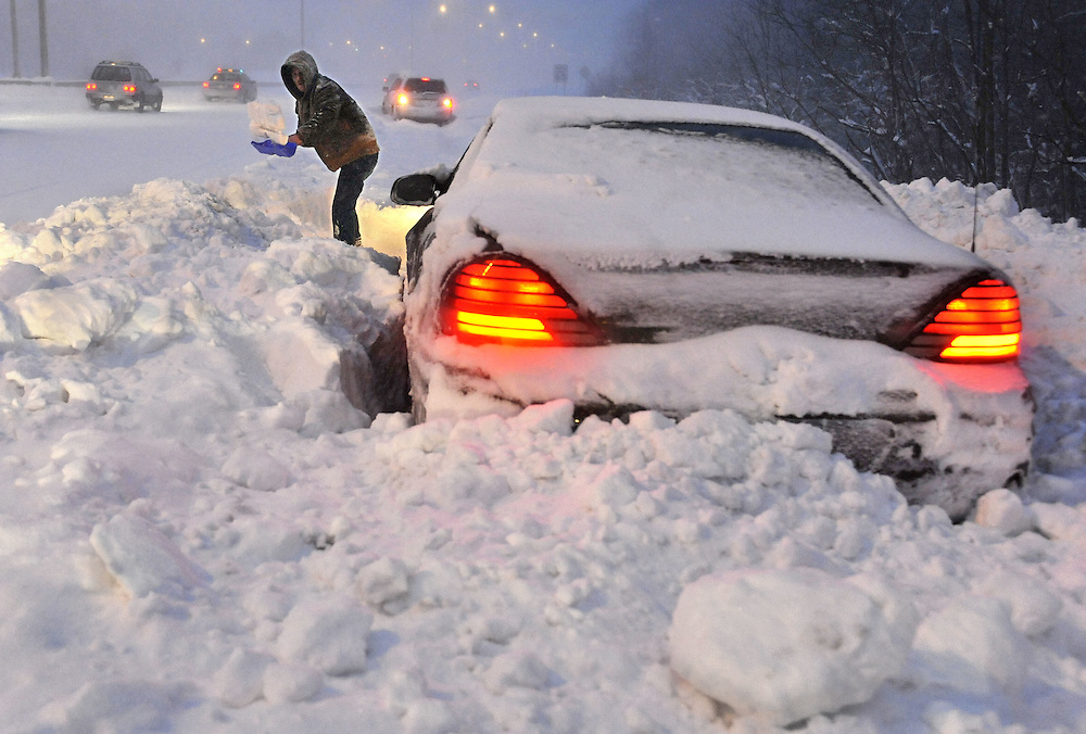 Roy Williams of Westfield, Mass., shovels snow in front of his vehicle on a merge ramp on Interstate 91 southbound during a winter storm in Windsor, Conn. Williams said a plow clearing the highway passed by and blocked him in. (AP Photo/Jessica Hill)