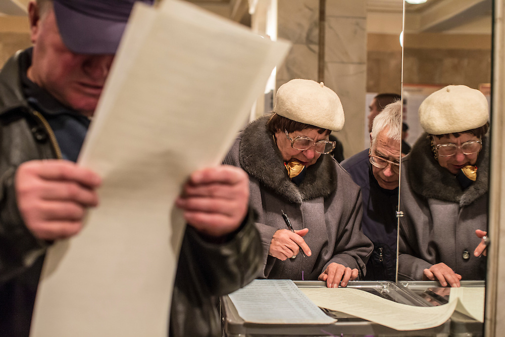 KIEV, UKRAINE - OCTOBER 26: Voters examine ballots for parliamentary elections at a polling station on October 26, 2014 in Kiev, Ukraine. Although a low turn out is expected in the east of the country, amid continued fighting between Ukrainian forces and pro-Russian seperatists, Ukraine is expected to elect a pro-western parliament in a further move away from Russian influence. (Photo by Brendan Hoffman/Getty Images) *** Local Caption ***