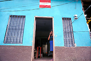 A woman peers out of her doorway near the Rio Choluteca (Choluteca River) in Tegucigalpa, Honduras in November 1998. Hurricane Mitch left upwards of 11,000 dead and hundreds of thousands homeless in Honduras, Nicaragua, and the rest of Central America. Floods and mudslides have leveled houses, buried villages and washed out major roadways and bridges, cutting off the northern and southern regions of Honduras.