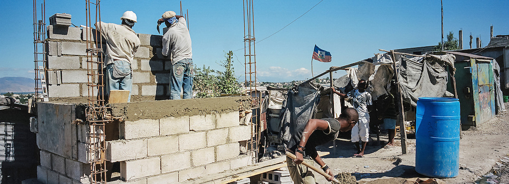 Men build a shop that will sell clean water in the Fort National neighborhood on Thursday, December 18, 2014 in Port-au-Prince, Haiti. Fort National was among the hardest hit areas of Port-au-Prince in the 2010 earthquake, but rebuilding has been slow to non-existent. Residents still mostly lack electricity and running water.