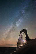 A person standing under Delicate Arch in Arches National Park photographed at night under the Milky Way and a sky full of stars.