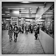 Commuters leave the secured area of the train station to head out into Shinjuku under the unblinking eye of a security camera.  Shinjuku Station, Tokyo, Japan.