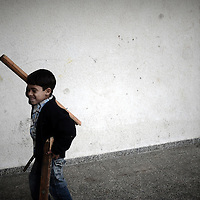 A Palestinian schoolboy carries pieces of wood as he cleans his damaged classroom at UNRWA's (UN Relief and Works Agency) primary school in Beit Lahia in the northern Gaza Strip on January 24, 2009. Some 200,000 Gaza children returned to school for the first time since Israel's offensive, many having lost family members, their home and their sense of security. The main UNRWA centre and several schools were destroyed by Israeli bombing during the 22-day war.