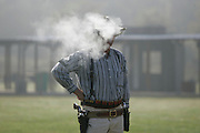 Dennis Ely, a member of the Scioto Territory Desperados from Piqua, Ohio, takes a puff from his cigar prior to the shooting match at TNT Sports Park south of Chillicothe on  Sept. 17, 2006.