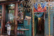 A priest walks out of a Hindu Temple at the end of Sea Street, near Colombo 13. A child runs out of an alley that leads to very high density housing, where a Catholic banner to Virgin Mary is strung between two bamboo poles.