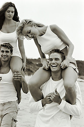 two couples enjoying piggyback rides on the beach