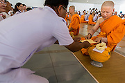 19 JULY 2014 - KHLONG LUANG, PATHUM THANI, THAILAND: A man makes merit by giving a donation to a  newly ordained novice at Wat Phra Dhammakaya. Seventy-seven men from 18 countries were ordained as Buddhist monks and novices at Wat Phra Dhammakaya, a Buddhist temple  north of Bangkok, Saturday. It is the center of the Dhammakaya Movement, a Buddhist sect founded in the 1970s and led by Phra Dhammachayo (Phrathepyanmahamuni). It is the largest temple in Thailand. The Dhammakaya sect has an active outreach program that attracts visitors from around the world.   PHOTO BY JACK KURTZ