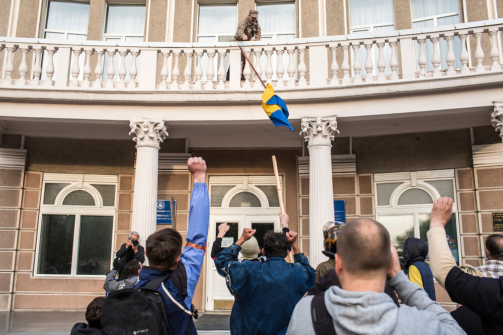 DONETSK, UKRAINE - MAY 4: Pro-Russian protesters take down a Ukrainian flag from a building during a march to the military prosecutor's office on May 4, 2014 in Donetsk, Ukraine. Cities across Eastern Ukraine have been overtaken by pro-Russian protesters in recent weeks, leading the Ukrainian military to respond with force in some areas. (Photo by Brendan Hoffman for The Washington Post)