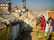 04 MARCH 2017 - KATHMANDU, NEPAL: A resident of an IDP camp in the center of Kathmandu walks through the camp. The camp opened days after the April 2015 earthquake devastated Nepal, killing almost 9,000 people. At its peak, about 1,800 families lived in the camp. The camp is still open nearly two years after the earthquake, about 400 families currently live in the camp. Camp residents say the Kathmandu municipal government is trying to close the camp and is encouraging residents to find new housing. They said the government is cutting off services to the camp and last week stopped the free distribution of water, although water can be purchased for delivery. Most of the people in the camp came to Kathmandu from rural villages in the mountains in the weeks after the earthquake. Many of the residents of the camp, technically homeless, have found work in Kathmandu's bustling construction industry, rebuilding homes destroyed in the earthquake.       PHOTO BY JACK KURTZ