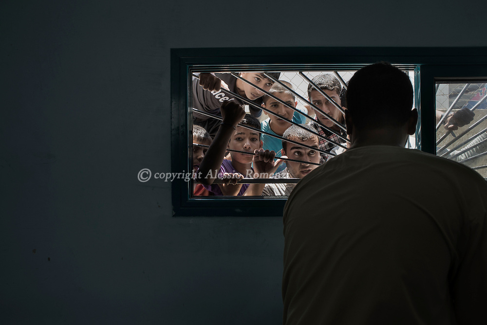 Gaza Strip, Beit Hanun: People are seen as they look trough the window of Beith Hanun  morgue on July 9, 2014. ALESSIO ROMENZI