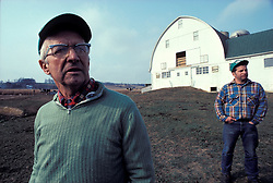Two generations of farming, father and son look over their acreage and livestock.