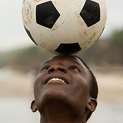 Man balancing football on his head in Accra, Ghana.