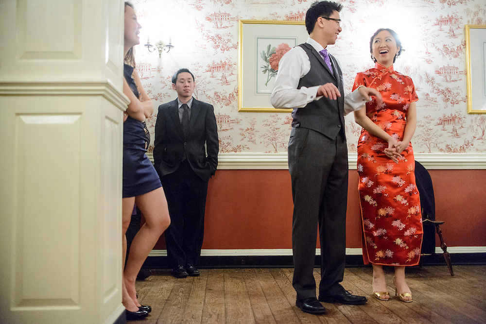 Photo by Matt Roth.Assignment ID: 30140754A..Michael Wong and Evelyn Hsieh, right, react during best man Justin Leung's (out of frame) speech during their reception at the the Mount Vernon Inn, in Mount Vernon, Virginia on Saturday, April 06, 2013. Evelyn changed from her white wedding dress to a traditional red Chinese wedding dress before the cake cutting.