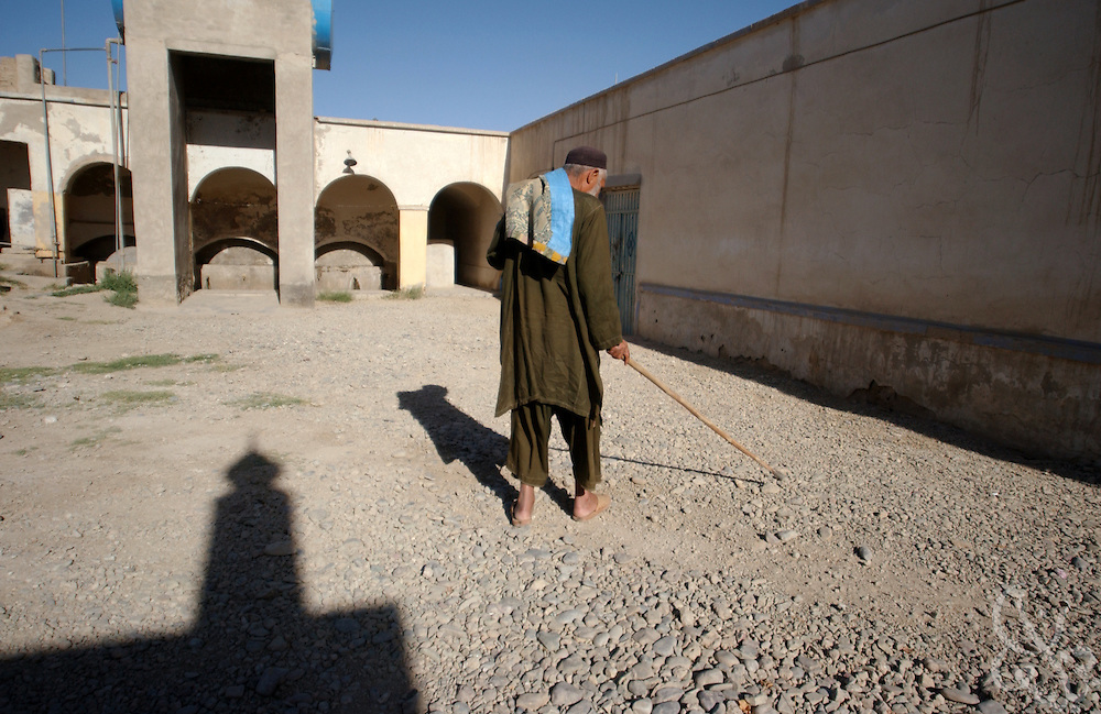A blind Afghan man crosses a courtyard using a walking stick inside the blind ward of the Afghanistan Red Crescent Society May 16, 2002 in Kandahar. The man has resided at the Society for approximately 35 years. Six others are in the ward as well.