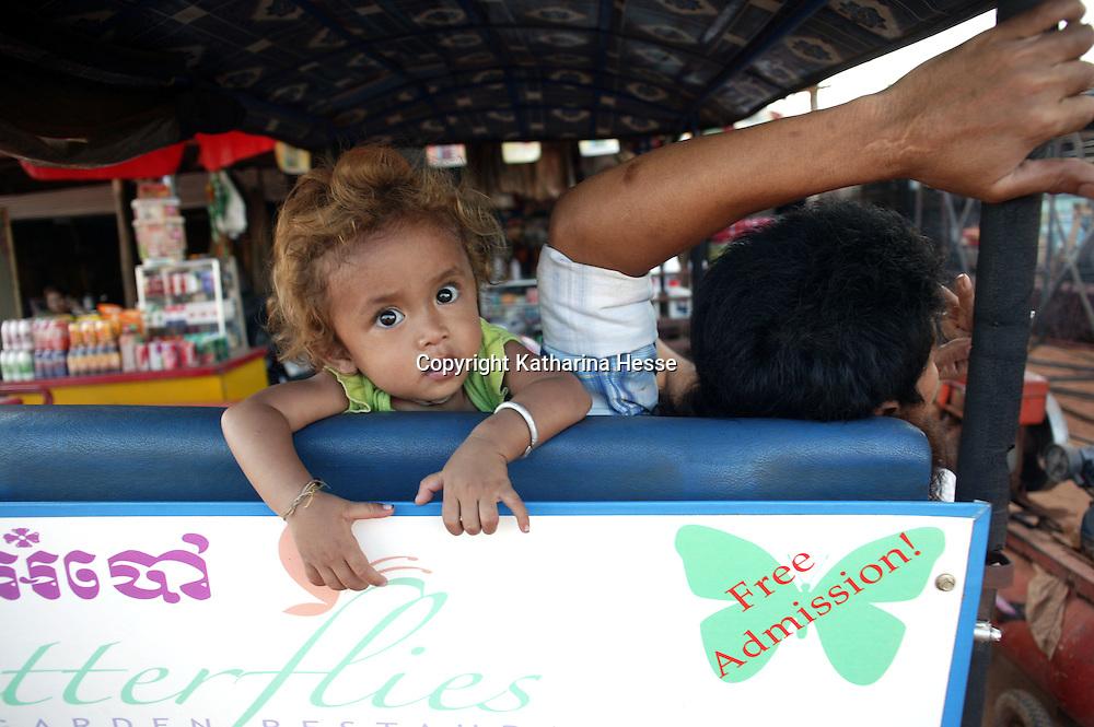 SIEM REAP, NOVEMBER-27:  a little girl sits next to her father in a pedicab in Siem Reap, November 28, 2006, Cambodia.