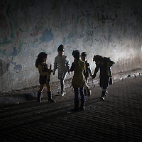 Young girls playing on the street are illuminated by a car's head light. Bambine giocano per la strada illuminate dai fari di una macchina.