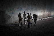 Young girls playing on the street are illuminated by a car's head light. Bambine giocano per la strada illuminate dai fari di una macchina.