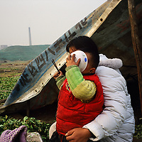 Migrant family from Henan Province living on land soon to be cleared for the 2008 Beijing Olympics...From China [sur]real © Mark Henley..