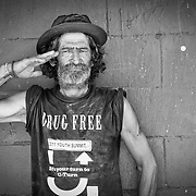 A homeless man makes a military salute as he explains his early years in the Puerto Rico National Guard.