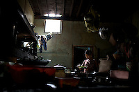 A young girl prepares greens for a customer at her family's restaurant in Mrauk U, Myanmar.
