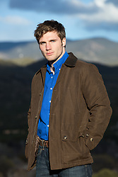 good looking man outdoors in a jacket standing on a mountain