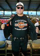 Joe Bridges shows off the signature tee-shirt while waiting for women to wrestle in chocolate sauce at a Harley-Davidson anniversary party in Milwaukee August 29, 2003. The legendary American motorcycle company is celebrating its 100th anniversary and is expected to draw 200,000 to 300,000 people to the company's home base over four days.    REUTERS/Rick Wilking