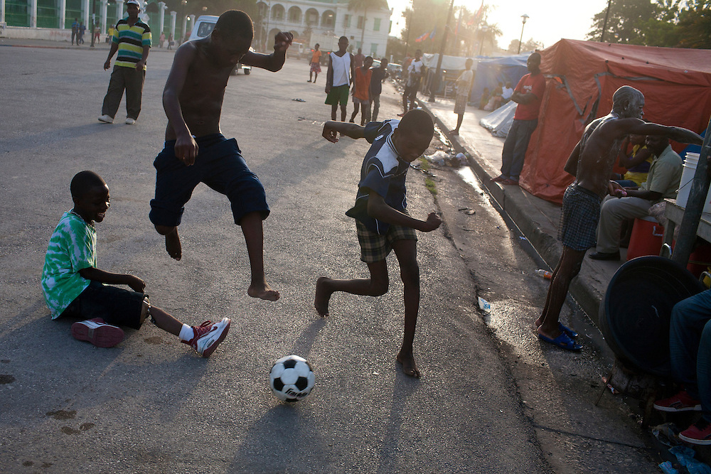 Boys, one of whom lost his leg in the earthquake and has a prosthesis (left), play soccer in front of the destroyed National Palace on July 9, 2010 in Port-au-Prince, Haiti.
