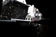 SYRIA, ALEPPO. A rebel sniper gestures showing the regime positions looking through a broken mirror in Bustan Al Bashar neighborhood in Aleppo . ALESSIO ROMENZI