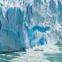 A massive chunk of ice calves from the face of the Perito Moreno Glacier into Lago Argentina.  One of only three advancing glaciers of Patagonia's 48, the Moreno, located in Parque Nacional Los Glaciares, creeps forward at a pace of around 2-3 meters per day.