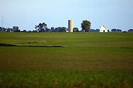 A small white barn stands out amongst the green fields on the plains of Illinois.