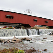 Bridgeton Historic District, Indiana: Bridgeton Covered Bridge (245 feet long) was rebuilt in historically accurate Burr Arch style in 2006 over Big Raccoon Creek (replacing 1868 bridge burnt by arson in 2005) on Bridgeton Road, Parke County, Indiana, USA. Bridgeton Mill was established 1823, rebuilt 1870, and is the oldest continuously operating mill west of the Allegheny Mountains. The mill grinds wheat into flour and corn into meal with 200 year-old French Buhr stones. Red and white painted wood. Dam and spillway. Panorama stitched from 5 photos.