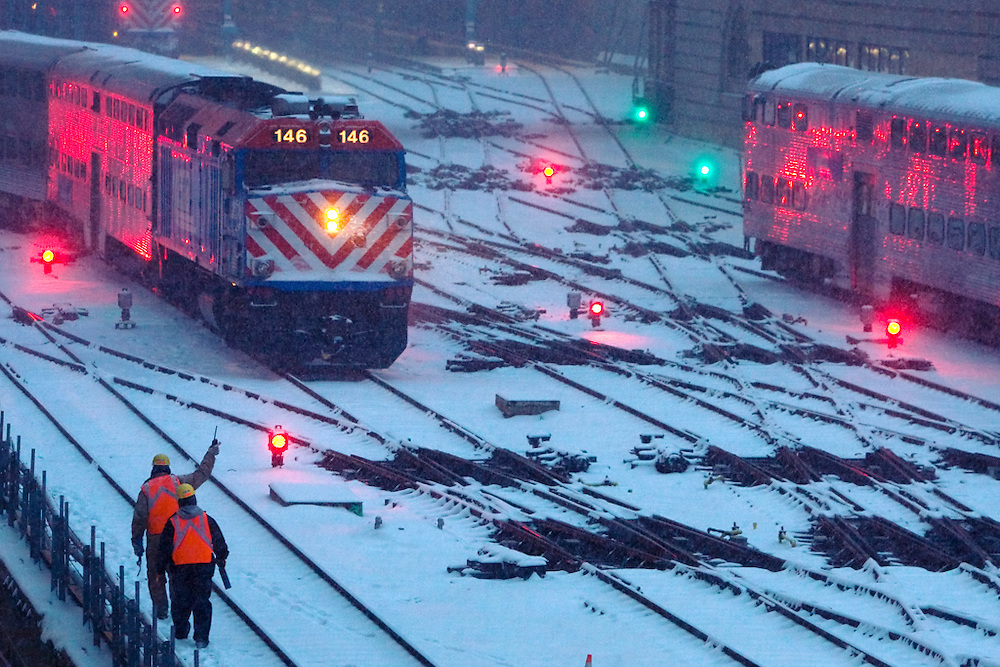 Inbound and outbound trains meet at the station throat at the Ogilvy Transportation Center in Chicago, IL as a worker gives a wave to the outbound train bound for the suburbs. A heavy snowfall is coming down in this mid December view.