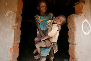 October 7, 2006 - Two children stand in the doorway to their home in Tetugu camp for internally displaced people, or IDP, near Gulu in north Uganda. Tetugu, with a population of 22,000, is one of 76 IDP camps around Gulu, the main base for the Uganda Peoples Defense Force fighting the insurgent Joseph Kony's Lord's Resistance Army. Kony's LRA movement has been fighting for the past 20 years to force the East African country to be ruled according to the Christian Ten Commandments. Over 2 million people, mostly of the Acholi tribe, have moved or were forced to move from their villages to camps close to the towns of Gulu, Lira, and Kitgum where they are watched over by the Ugandan Army. The LRA rebels have abducted thousands of children and have forced them to fight against the Ugandan Army and the Acholi people. Current peace talks between Kony's LRA and the Ugandan government held in Juba, southern Sudan, offer a glimpse of hope to ending this ongoing conflict..(Photo by Jakub Mosur/Polaris)<br />