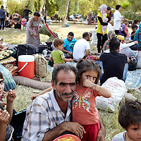 Syrian refugee Mohammed Abdul Halim, and his daughter Kima Mohammed Halim, 4-years-old, and members of their family from Hassakeh, Syria who spent several days and nights living outdoors in a makeshift campsite in Qushtapa Park wait to be transferred to a tented settlement in Qushtapa, Iraq outside of Erbil in Iraqi Kurdistan, Monday, September 2, 2013.  September 2013.