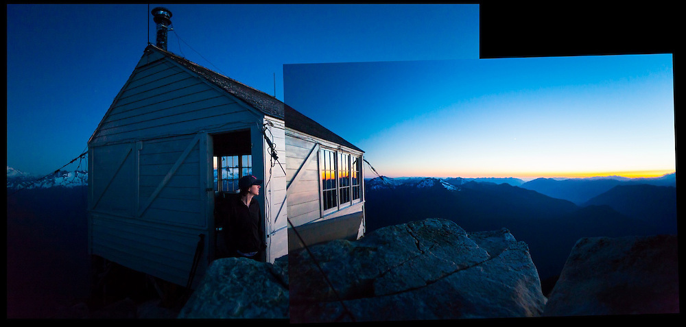 A young woman watches the sunset from the fire lookout cabin on the summit of Hidden Lake Peaks, North Cascades National Park, Washington.