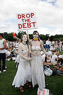 MAKE POVERTY HISTORY Two young protesters contribute to the campaign effort all in White! .Date picture taken 2nd July Edingburgh make poverty history Rally. photo published in The Newstatesman 11july 2005 The biggest ever anti-poverty movement came together under the banner of MAKEPOVERTYHISTORY in 2005 calling for urgent action for more and better aid, debt cancellation and trade justice.<br /> Millions of people wore white bands, 444,000 people emailed the Prime Minister about poverty and 225,000 took to the streets of Edinburgh for the Make Poverty History march and rally.<br /> The campaign ensured that global poverty was placed higher on the national and global agenda than ever before.