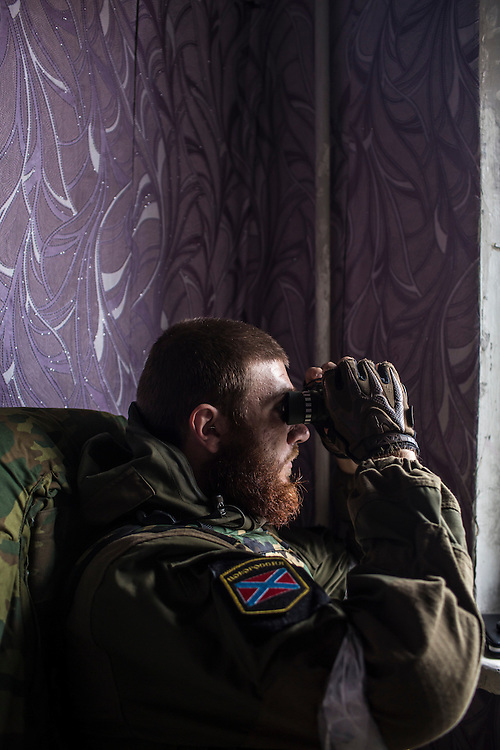 A pro-Russian rebel fighter uses binoculars to watch from an apartment building where he and other militiamen can observe and coordinate fighting to gain control of the Donetsk airport on Friday, October 17, 2014 in Donetsk, Ukraine. Photo by Brendan Hoffman, Freelance