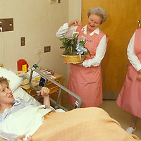 Volunteers in the Dekalb General Hospital in Atlanta deliver a plant to a patient in the maternity ward in March 1987.