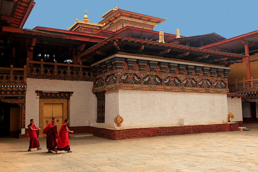 Asia, Bhutan, Punakha. Three monks walk across Punakha Dzong courtyard Assembly Hall.